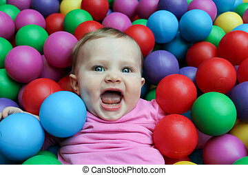 Cute baby playing in ball pit - Cute baby girl playing with...