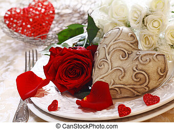 Place Setting with a place card, red and white roses and a...