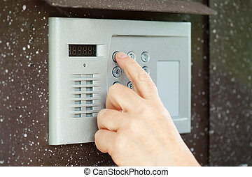finger pushing button of intercom - Human finger pushing...