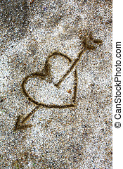 heart and arrow drawn in the sand
