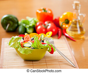 greek salad, vegetables and bottle with sunflower oil on wooden table