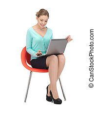 young businesswoman sitting in chair with laptop - picture...