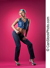 Cute sexy girl posing in jeans on pink background