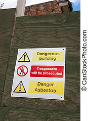 Asbestos Danger Sign calls attention to a hazardous building...