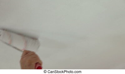House Painter At Work - Hand holding a paint roller and...