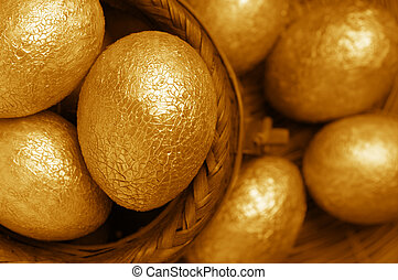 Golden Easter eggs with craquelures in wicker basket.