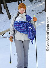 Cross contry skiing with sling and newborn baby in winter