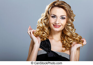 Young woman in black dress with curly hair