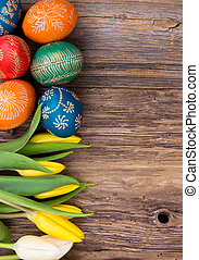 Easter background - Hand-painted easter eggs with tulips on...