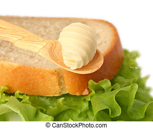 Butter curl on wooden spoon with bread