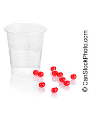 Pharmacy. Red vitamin pills and plastic cup of water