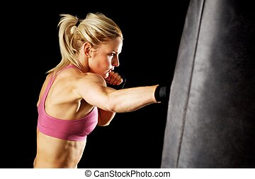 Punching Bag Punch - Young woman making a hard punch on a...