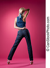 sexy blond woman posing in jeans on pink