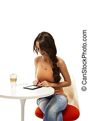 beautiful woman at a table with latte macchiato reading...