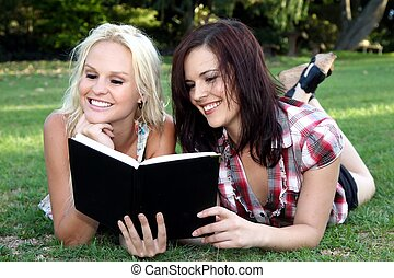 Beautiful Young Women Friends Reading Outdoors