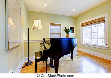 Living room with black piano and large window.