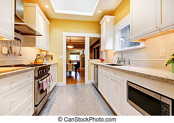 Yellow and white simple kitchen with skylight - Narrow white...