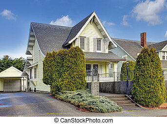 Craftsman style yellow house exterior.