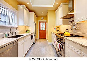 Yellow and white narrow modern kitchen.