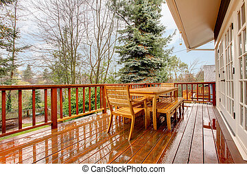 Wood deck with furniture and grey house. - Wood deck during...