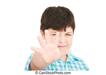 Child looking at camera. Stop signal with his hand.  Boy trying to defend himself isolated on white