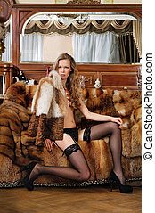 Beautiful woman in fur coat in a luxurious classical interior.