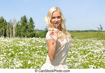 Beautiful  woman on the meadow with bubbles
