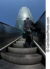 Man approaching business building from below with escalator