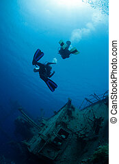 Divers exploring ship wreck