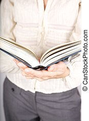 woman white shirt detail holding an open book