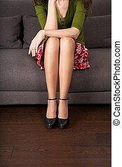 woman detail sitting on a brown sofa