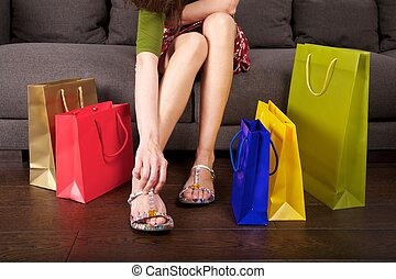 woman detail sitting on a brown sofa between shopping bags