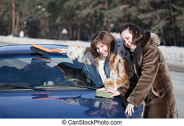 women cleaning car in winter day