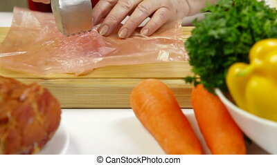 Tenderizing Chicken Breast On Cutting Board