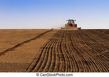 Agriculture tractor sowing seeds and cultivating field in...