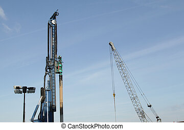Pile driver and crane - A blue painted pile driver and a...