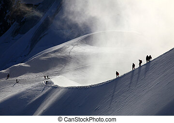 A group of alpinists on their way to the mont blanc at dawn