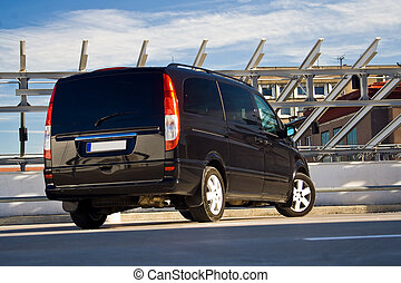 black minivan - rear view of a black minivan on a parking...