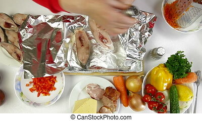 Cooking Baked Fish - Female hands cooking baked fish - add...