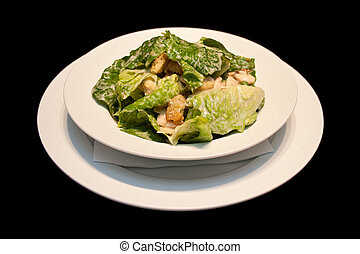 Caesar salad with shrimps on a white plate isolated on black