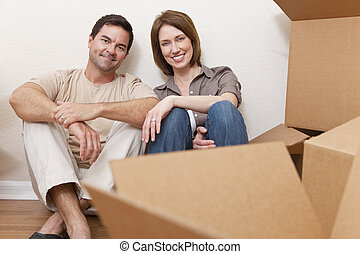 Happy Couple Unpacking or Packing Boxes Moving House - Happy...
