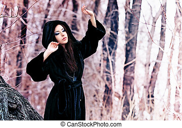 fur - Shot of a gothic woman in a winter park. Fashion.