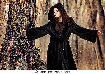 witch - Shot of a gothic woman in a winter park. Fashion.