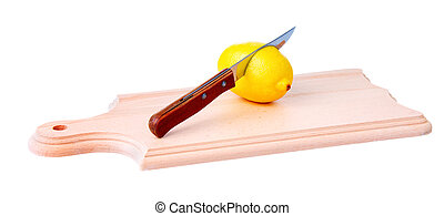 Knife pierces a lemon on wooden plank - Knife pierces a...