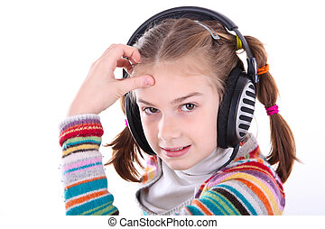 Happy little girl in headphones listens to music