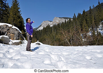 A trekking girl in the snowy mountains in the Carpathians,...