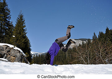 Young woman doing a cartwheel in the snow, in the mountains...