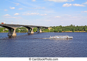 small promenade motor ship on big river near bridge
