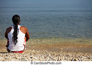 Peace - Young man sitting on the beach enjoying peaceful...