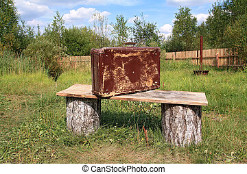 old valise near wooden bench